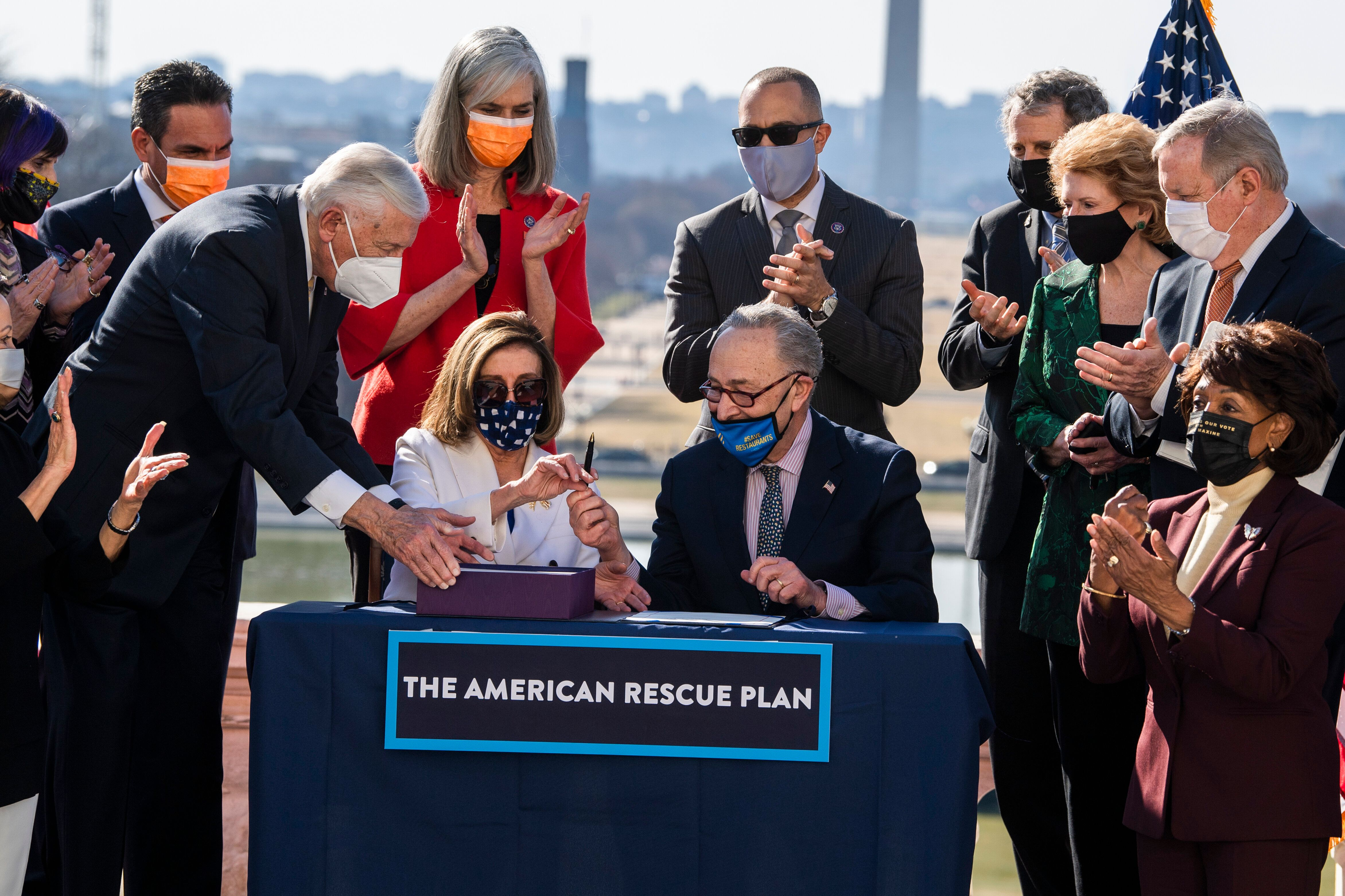 Speaker of the House Nancy Pelosi (D-Calif.) and Senate Majority Leader Chuck Schumer (D-N.Y.), center, sign the American Res