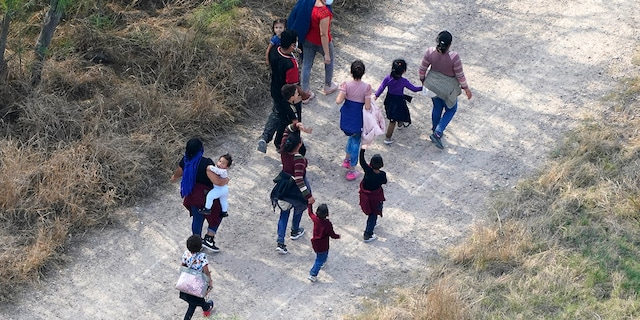 Migrants walk on a dirt road after crossing the U.S.-Mexico border, Tuesday, March 23, 2021, in Mission, Texas. A surge of migrants on the Southwest border has the Biden administration on the defensive. The head of Homeland Security acknowledged the severity of the problem but insisted it's under control and said he won't revive a Trump-era practice of immediately expelling teens and children. (AP Photo/Julio Cortez)