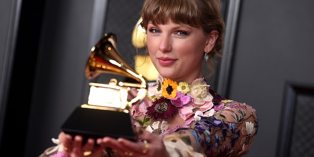 """Taylor Swift poses in the press room with the award for album of the year for """"Folklore"""" at the 63rd annual Grammy Awards at the Los Angeles Convention Center on Sunday, March 14. A spokesperson for the artist confirmed to Fox News on Thursday that she and Evermore Park in Utah have dropped their respective lawsuits against one another."""