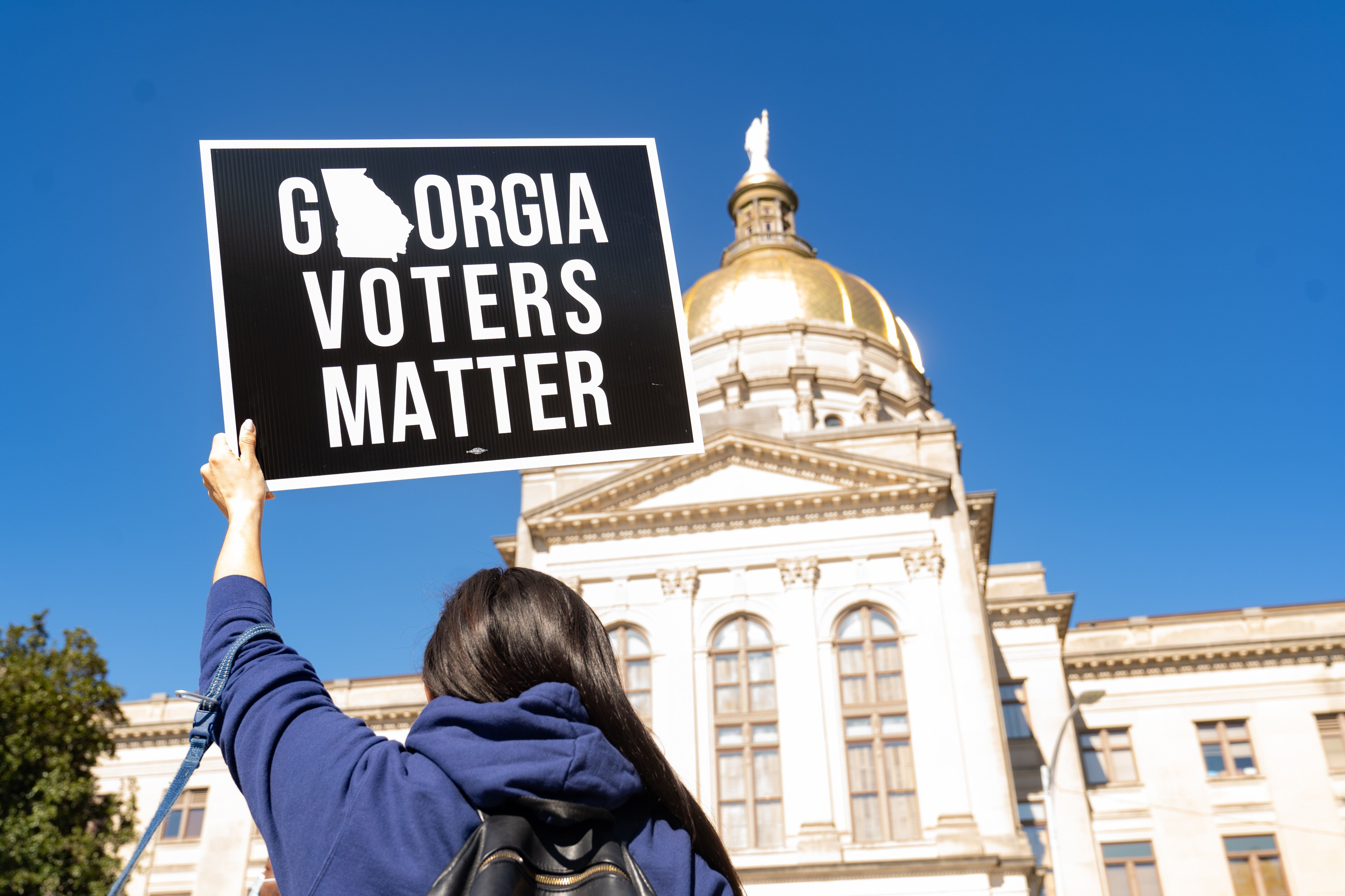 A demonstrator stands outside of the Georgia Capitol building in Atlanta on March 3, to oppose a measure that would dramatica