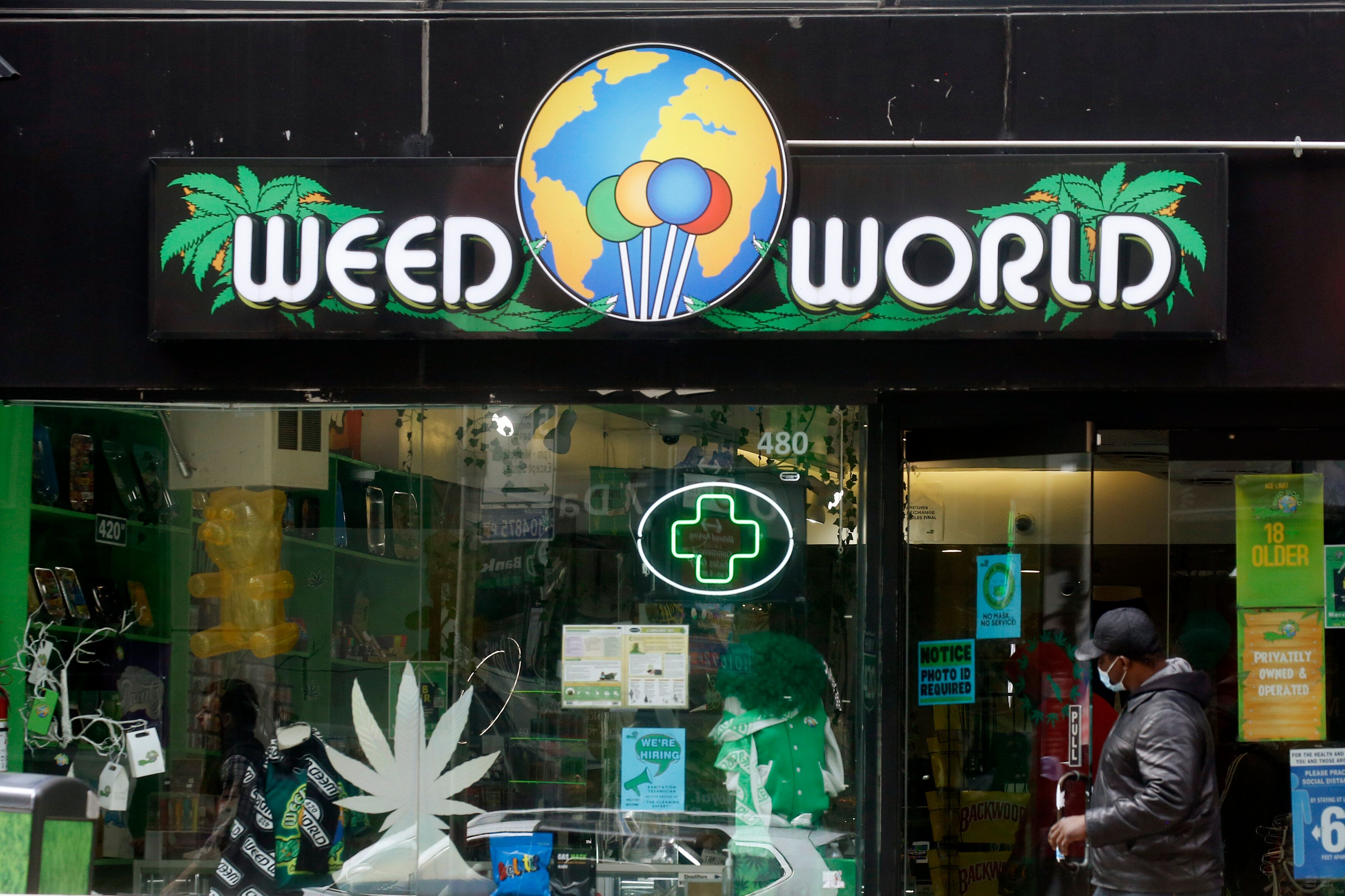 A man opens the door of the Weed World Store in New York City on Thursday. New York State has reached a deal to legalize recr