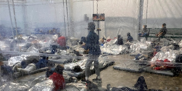 This March 20, 2021, photo provided by the Office of Rep. Henry Cuellar, D-Texas, shows detainees in a Customs and Border Protection (CBP) temporary overflow facility in Donna, Texas.