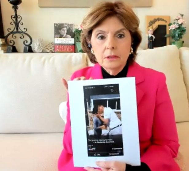 Gloria Allred displaying a photo of Gov. Andrew Cuomo (D) kissing Sherry Vill.