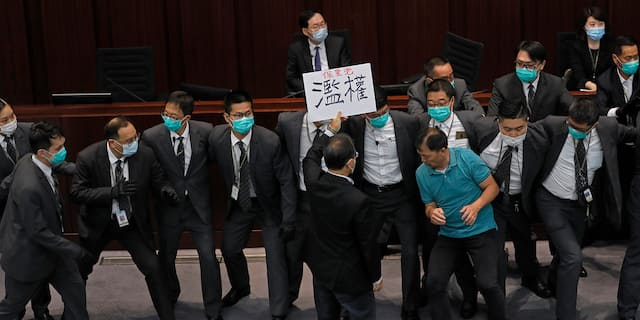 Pro-democracy lawmaker Wu Chi-wai, right in a polo shirt, scuffles with security guards during a Legislative Council's House Committee meeting in Hong Kong on May 18, 2020. (AP Photo/Vincent Yu, File)
