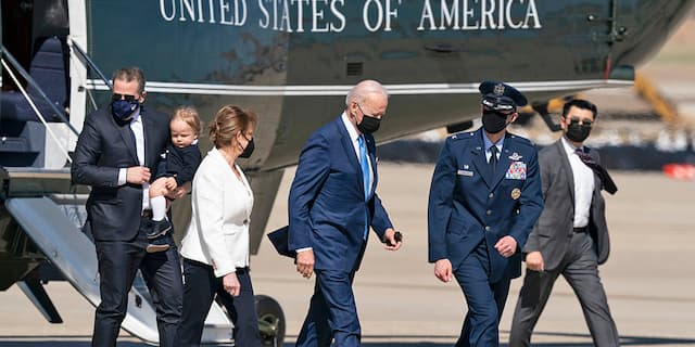 President Joe Biden, center, walks from Marine One to board Air Force One, with son Hunter Biden, left, as he carries his son Beau, Friday, March 26, 2021, at Andrews Air Force Base. (AP Photo/Alex Brandon)