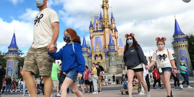 A family walks past Cinderella Castle in the Magic Kingdom, at Walt Disney World in Lake Buena Vista, Fla. (Joe Burbank/Orlando Sentinel via AP, File)