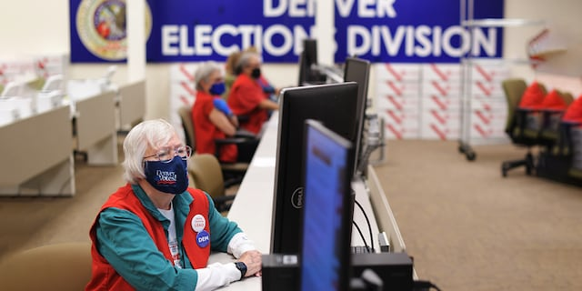 Election judge Mary Ann Thompson, front, is checking ballots at adjudication section at the Denver Elections Division in Denver, Colorado on Thursday. October 29, 2020. (Photo by Hyoung Chang/MediaNews Group/The Denver Post via Getty Images)