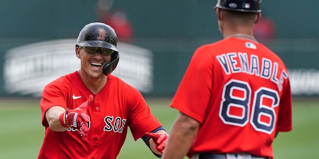 Boston Red Sox' Enrique Hernandez, left, reacts as he rounds the bases and runs towards third base coach Will Venable after hitting a home run in the third inning of Inning of a spring training baseball game against the Atlanta Braves on Monday, March 29, 2021, in North Port, Fla. (AP Photo/John Bazemore)