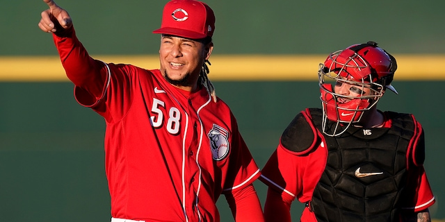 Cincinnati Reds starting pitcher Luis Castillo (58) walks to the dugout with catcher Tucker Barnhart after warming up in the bullpen prior to the team's spring training baseball game against the Chicago Cubs on Saturday, March 27, 2021, in Goodyear, Ariz. (AP Photo/Ross D. Franklin)