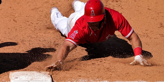 Los Angeles Angels' Mike Trout dives back safely on a pick-off attempt during the fifth inning of a spring training baseball game against the Milwaukee Brewers, Thursday, March 18, 2021, in Tempe, Ariz. (AP Photo/Matt York)
