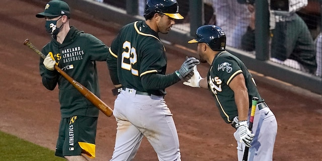 Oakland Athletics' Ramon Laureano (22) celebrates with Vimael Machin, right, and the bat boy while returning to the dugout after scoring against the Los Angeles Dodgers during the third inning of a spring training baseball game Friday, March 26, 2021, in Phoenix. (AP Photo/Ross D. Franklin)