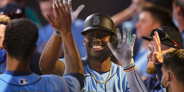 Seattle Mariners' Kyle Lewis, center, celebrates his solo home run with teammates in the dugout during the third inning of a spring training baseball game against the Chicago White Sox, Friday, March 19, 2021, in Peoria, Ariz. (AP Photo/Sue Ogrocki)