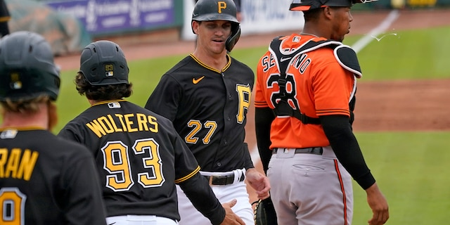 Pittsburgh Pirates' Kevin Newman (27) and Tony Wolters (93) score behind Baltimore Orioles catcher Pedro Severino (28) on a double by teammate Phillip Evans during the third inning of a spring training exhibition baseball game in Bradenton, Fla., Monday, March 22, 2021. (AP Photo/Gene J. Puskar)