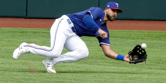 Texas Rangers center fielder Joey Gallo makes a diving catch against the Milwaukee Brewers during the third inning of a preseason baseball game Tuesday, March 30, 2021, in Arlington, Texas. (AP Photo/Michael Ainsworth)
