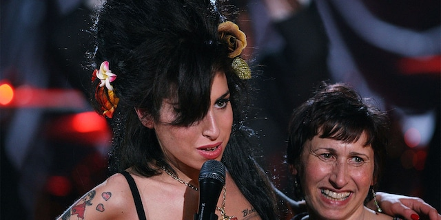 British singer Amy Winehouse (L) hugs her mother Janis Winehouse after accepting a Grammy Award at the Riverside Studios for the 50th Grammy Awards ceremony via video link on February 10, 2008, in London, England.