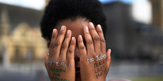 FILE - In this file photo dated Sunday, June 21, 2020, a woman symbolically covers her eyes as she participates in a Black Lives Matter protest calling for an end to racial injustice, at the Parliament Square in central London. (AP Photo/Alberto Pezzali)