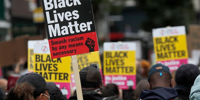"""FILE - In this file photo dated Sunday, Aug. 30, 2020, Black Lives Matter protesters hold posters as they march through Notting Hill during the """"Million People March"""" through central London. (AP Photo/Frank Augstein, FILE)"""