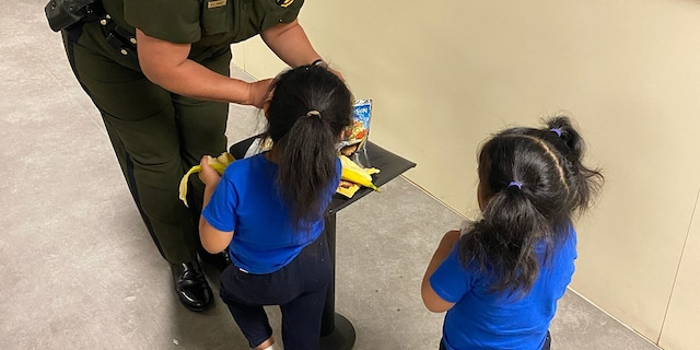 El Paso BP Sector Chief Gloria Chavez is giving girls, who were tossed from border wall, a snack inside the El Paso processing center.