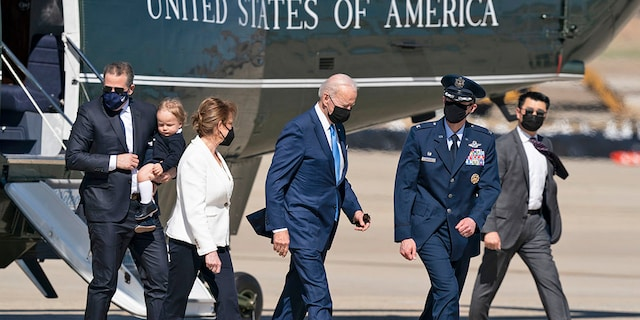 President Joe Biden, center, walks from Marine One to board Air Force One, with son Hunter Biden, left, as he carries his son Beau, Friday, March 26, 2021, at Andrews Air Force Base, Md. Biden is en route to Delaware. (AP Photo/Alex Brandon)