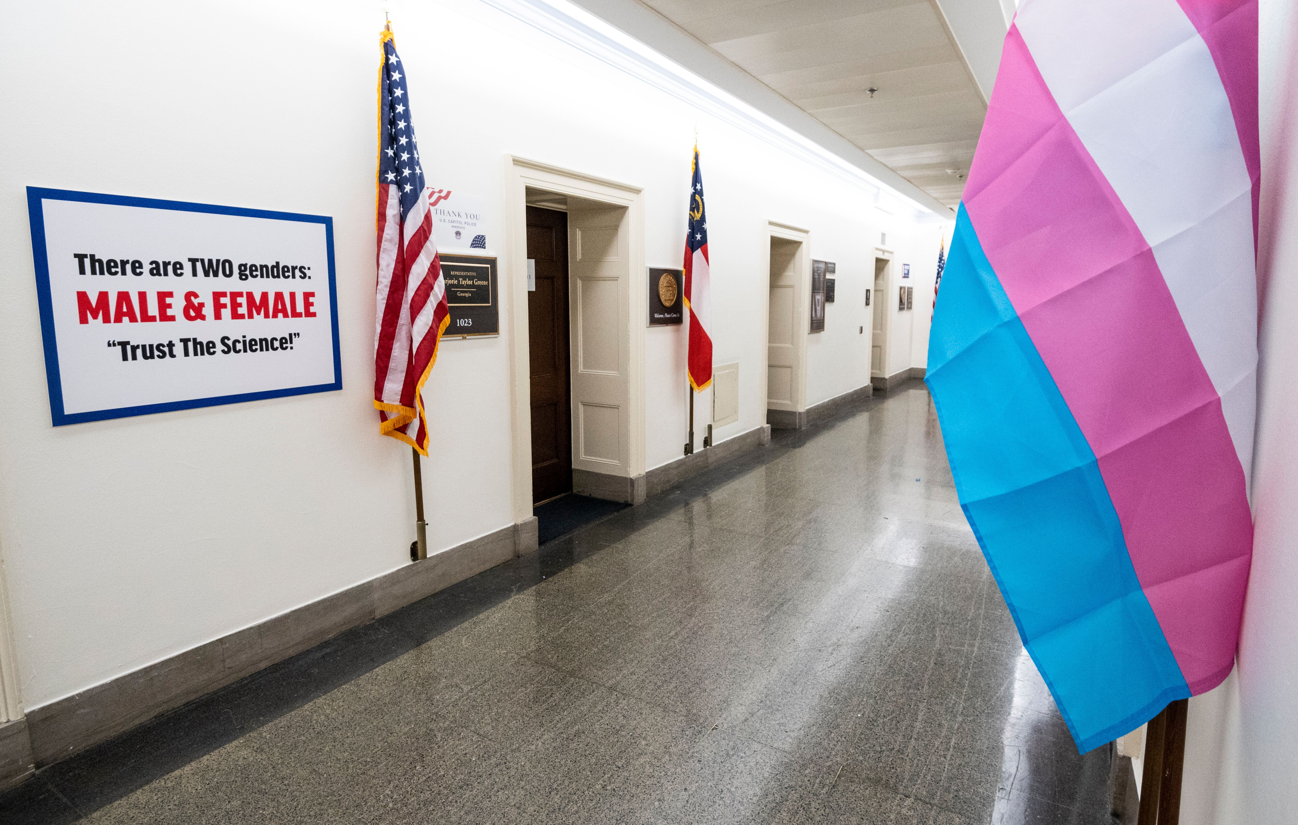 The transgender pride flag hangs across the hall from a transphobic sign outside the office of Rep. Marjorie Taylor Greene (R