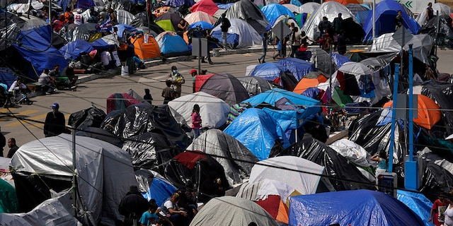 A makeshift camp of migrants sits at the border port of entry leading to the United States, Wednesday, March 17, 2021, in Tijuana, Mexico. (AP Photo/Gregory Bull)