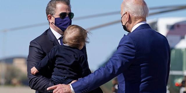President Joe Biden talks with his son Hunter Biden as he holds his grandson Beau Biden as they walk to board Air Force One at Andrews Air Force Base, Md., Friday, March 26, 2021. Hunter Biden is releasing a book detailing his this month.