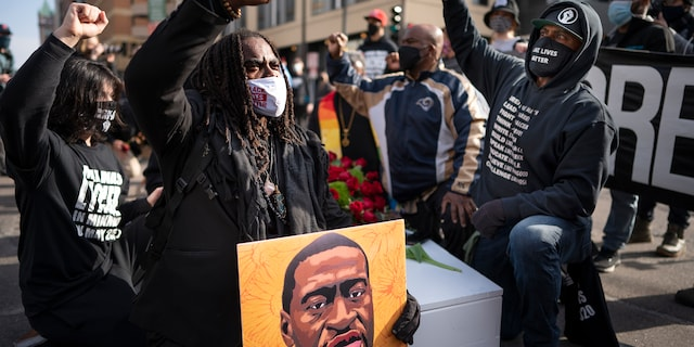Cortez Rice, left, of Minneapolis, sits with others in the middle of Hennepin Avenue on Sunday, March 7, 2021, in Minneapolis, Minn., to mourn the death of George Floyd a day before jury selection is set to begin in the trial of former Minneapolis officer Derek Chauvin, who is charged in Floyd's death. (Jerry Holt/Star Tribune via AP, File)