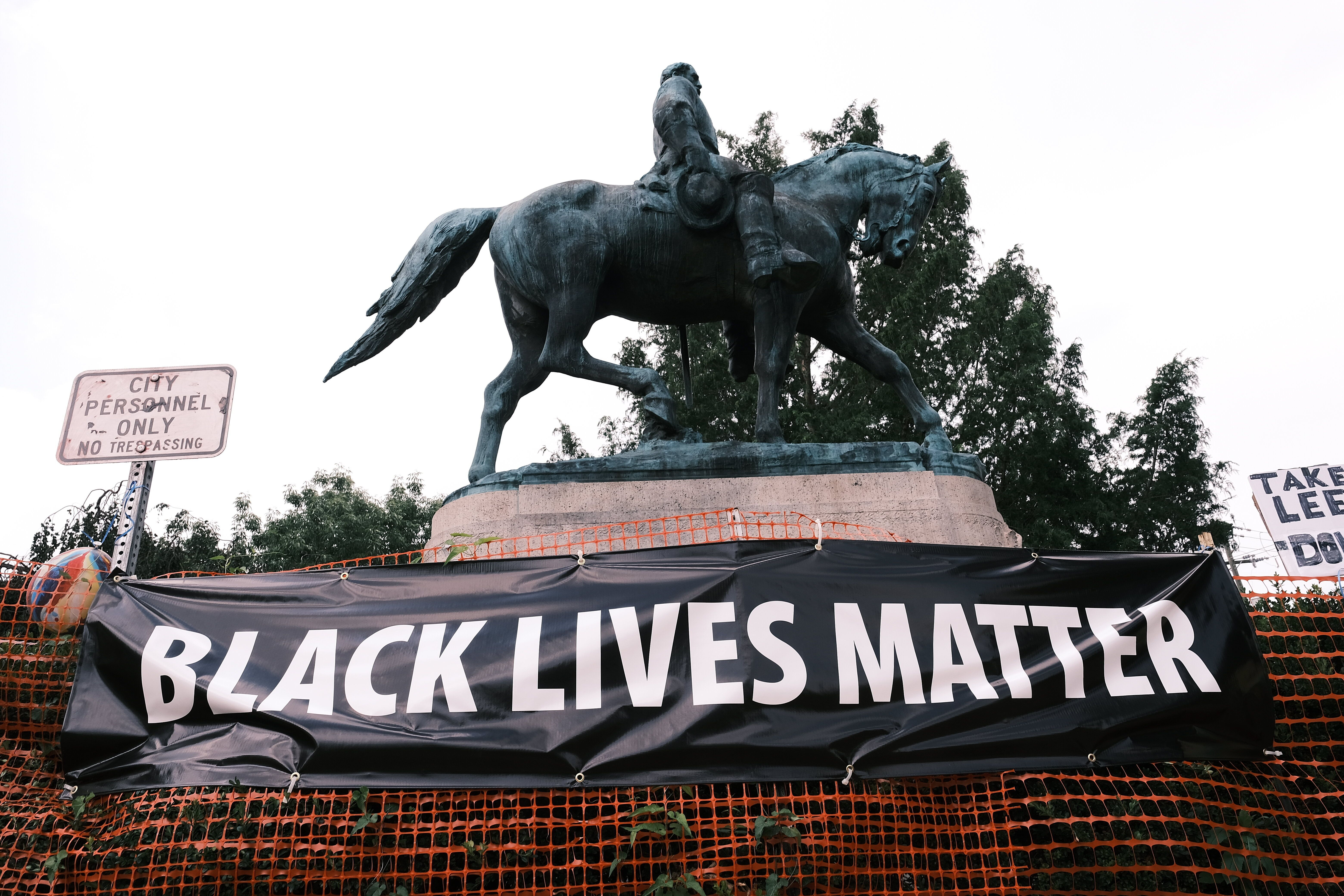 """A """"Black Lives Matter"""" banner hangs before a Robert E. Lee statue in Charlottesville, Virginia. McAuliffe backed the removal"""