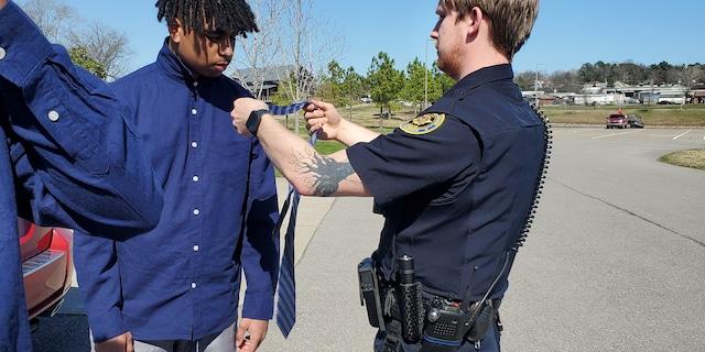 Officer Adam Price helps 18-year-old Elijah Darling tie a tie.