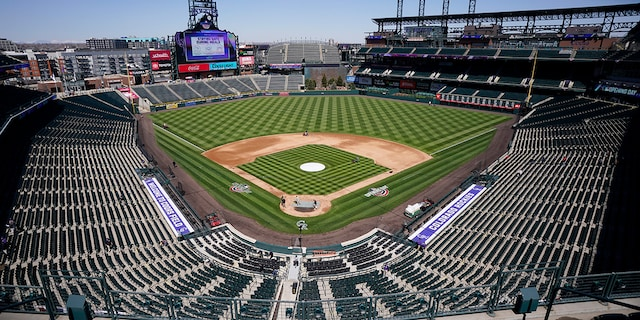 Workers prepare Coors Field on Wednesday, March 31, 2021, in Denver, the day before the Colorado Rockies' season-opener against the Los Angeles Dodgers. (Associated Press)