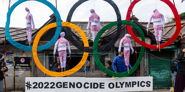 FILE - In this Feb. 3, 2021, file photo, exile Tibetans use the Olympic Rings as a prop as they hold a street protest against the holding of 2022 Winter Olympics in Beijing in Dharmsala, India. (AP Photo/Ashwini Bhatia, File)