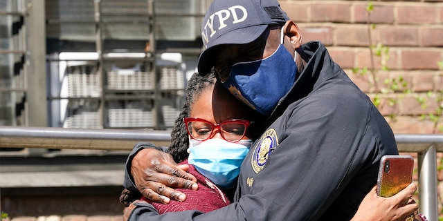 A police officer hugs a community leader outside the building where a man shot the mother of his child and two of her daughters dead before turning the gun on himself, Tuesday, April 6, 2021. (AP Photo/Mary Altaffer)