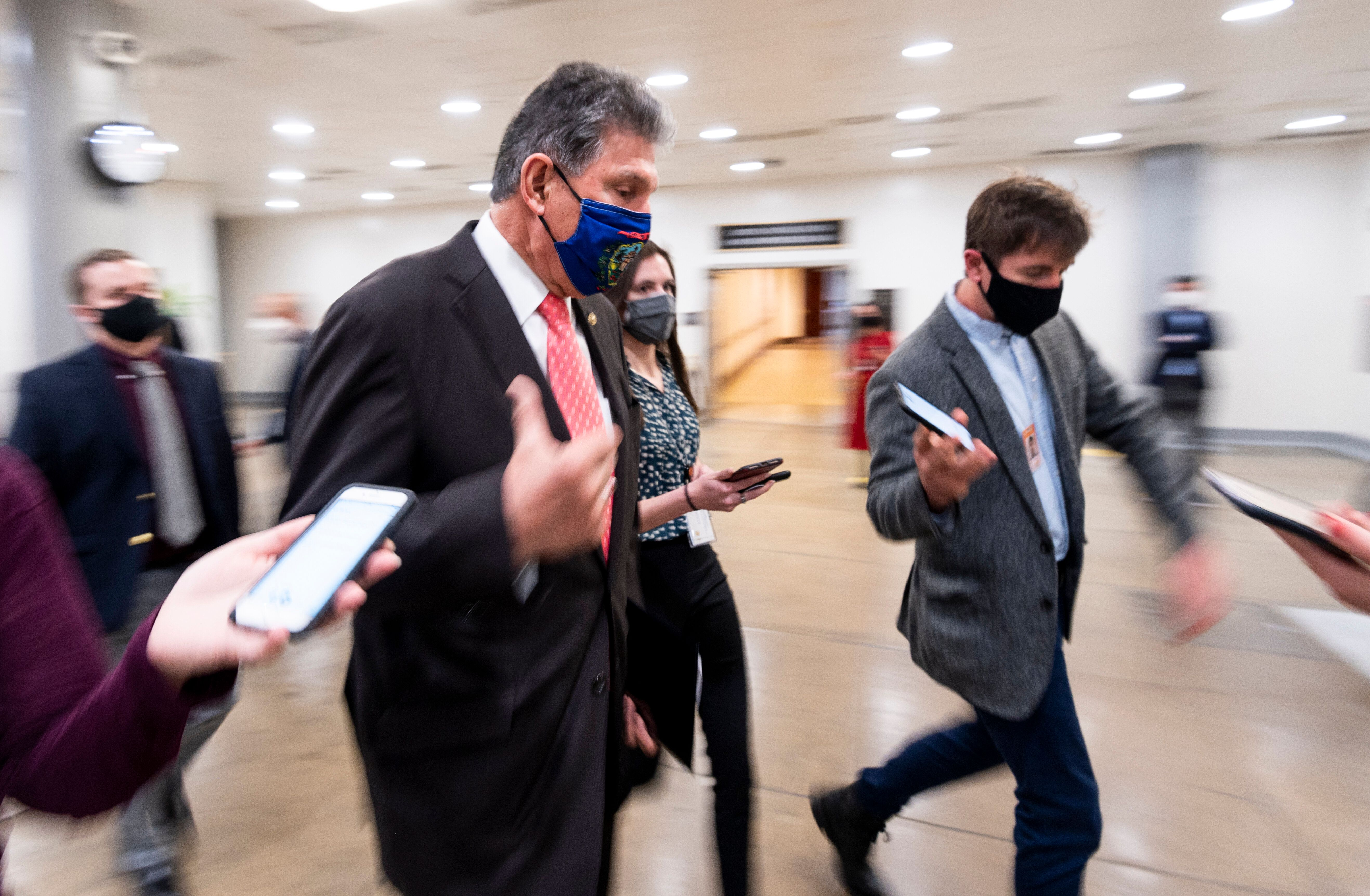 Sen. Joe Manchin (D-W.Va.) speaks with reporters in the Senate subway as he arrives for a vote in the Capitol on Wednesday, M