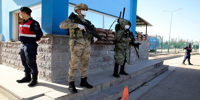 Soldiers stand in guard as people wait outside a courthouse before the trial of 497 defendants, in Sincan, Turkey, on Wednesday. (AP)