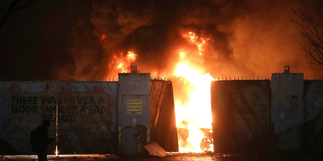 Hijacked cars burn at the peace wall on Lanark Way as rioting broke out in West Belfast, Northern Ireland, Wednesday, April 7, 2021. The police had to close roads into the nearby Protestant area as crowds from each divide, Nationalists and Loyalists, attacked each other. (Associated Press)