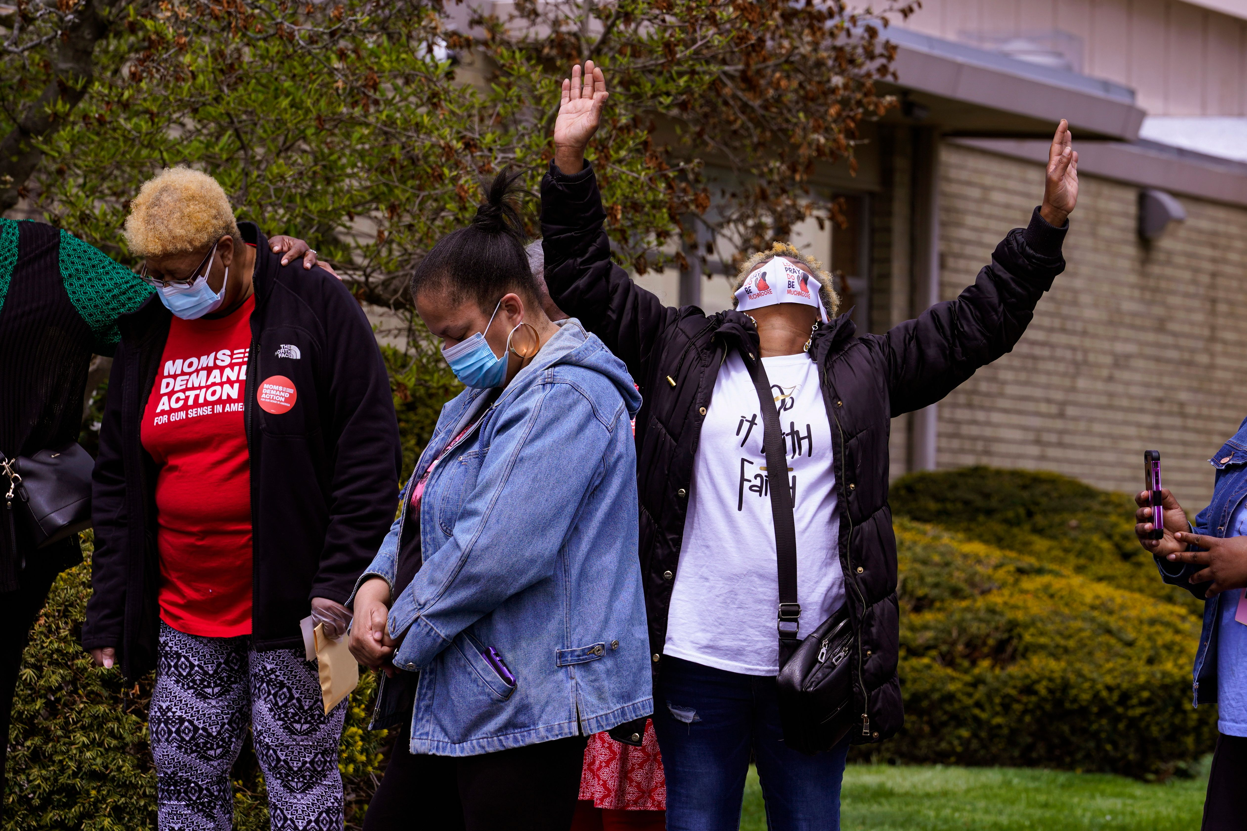 Connie Nance raises her arms in prayer during a vigil at the Olivet Missionary Baptist Church in Indianapolis, Saturday, Apri