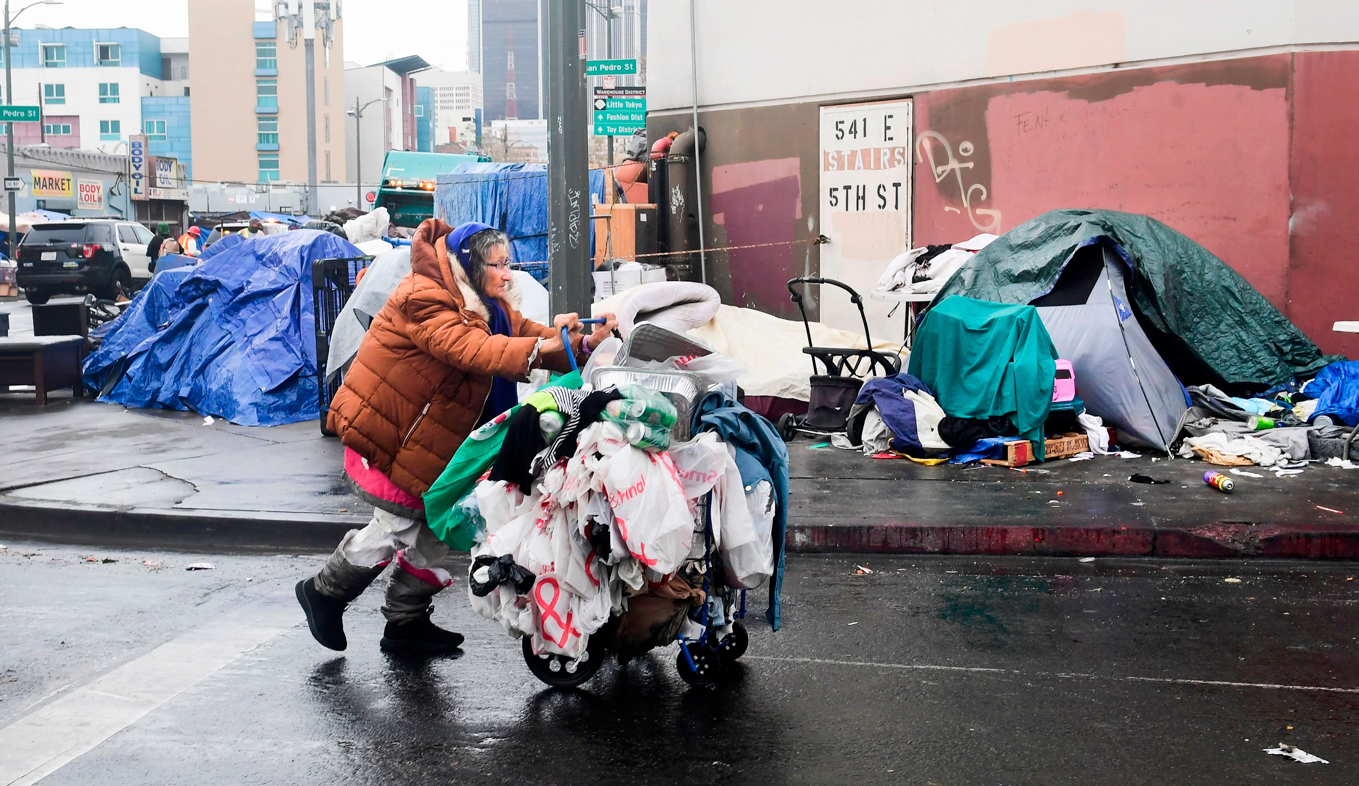 A woman pushes her belongings past a row of tents in Los Angeles on Feb. 1.At last count, more than 4,662 unhoused peop
