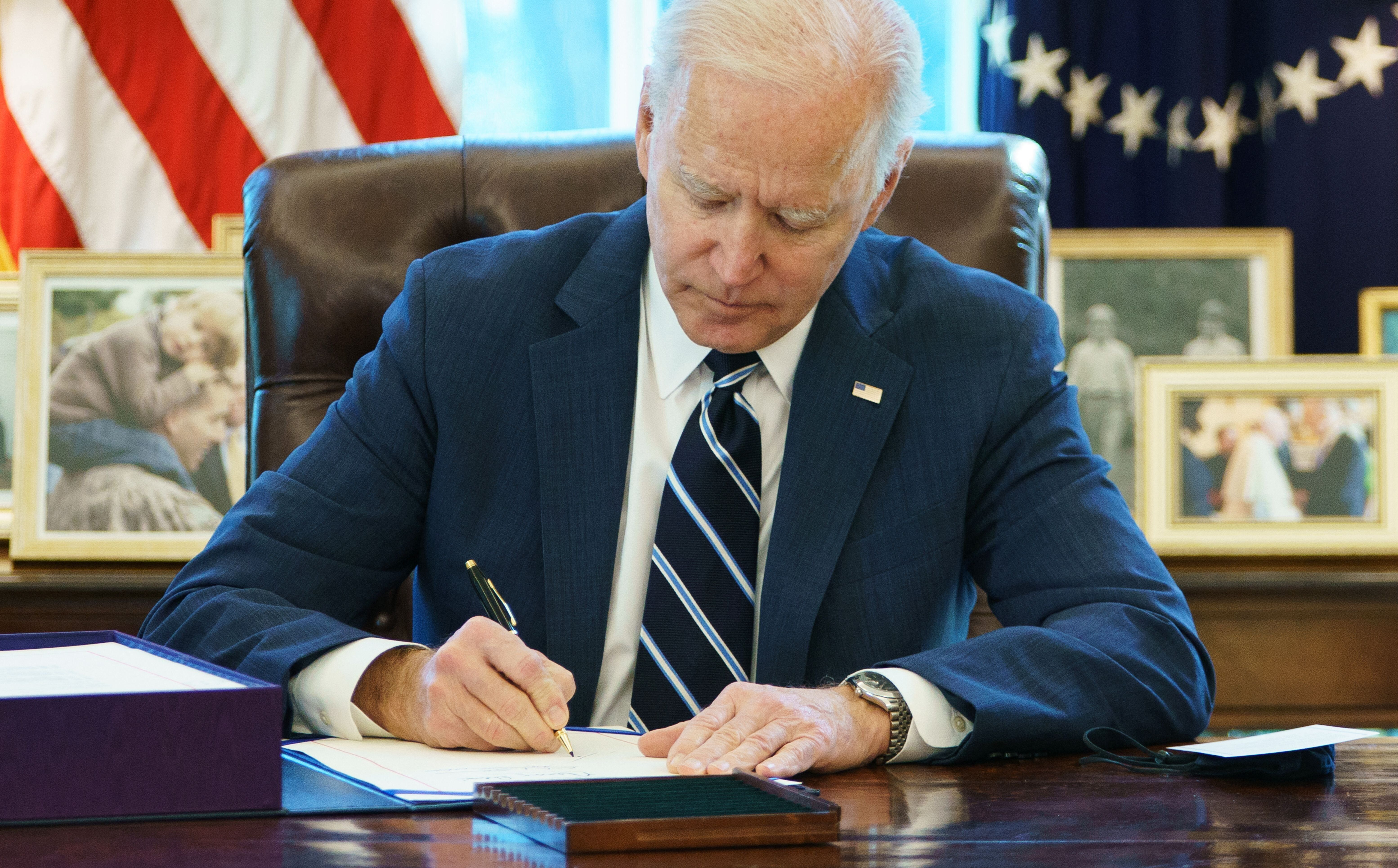 President Joe Biden signs the American Rescue Plan on March 11 in the Oval Office of the White House.