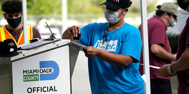 In this Oct. 26, 2020 file photo, an election worker stamps a vote-by-mail ballot dropped off by a voter before placing it in an official ballot drop box before at the Miami-Dade County Board of Elections in Doral, Florida.