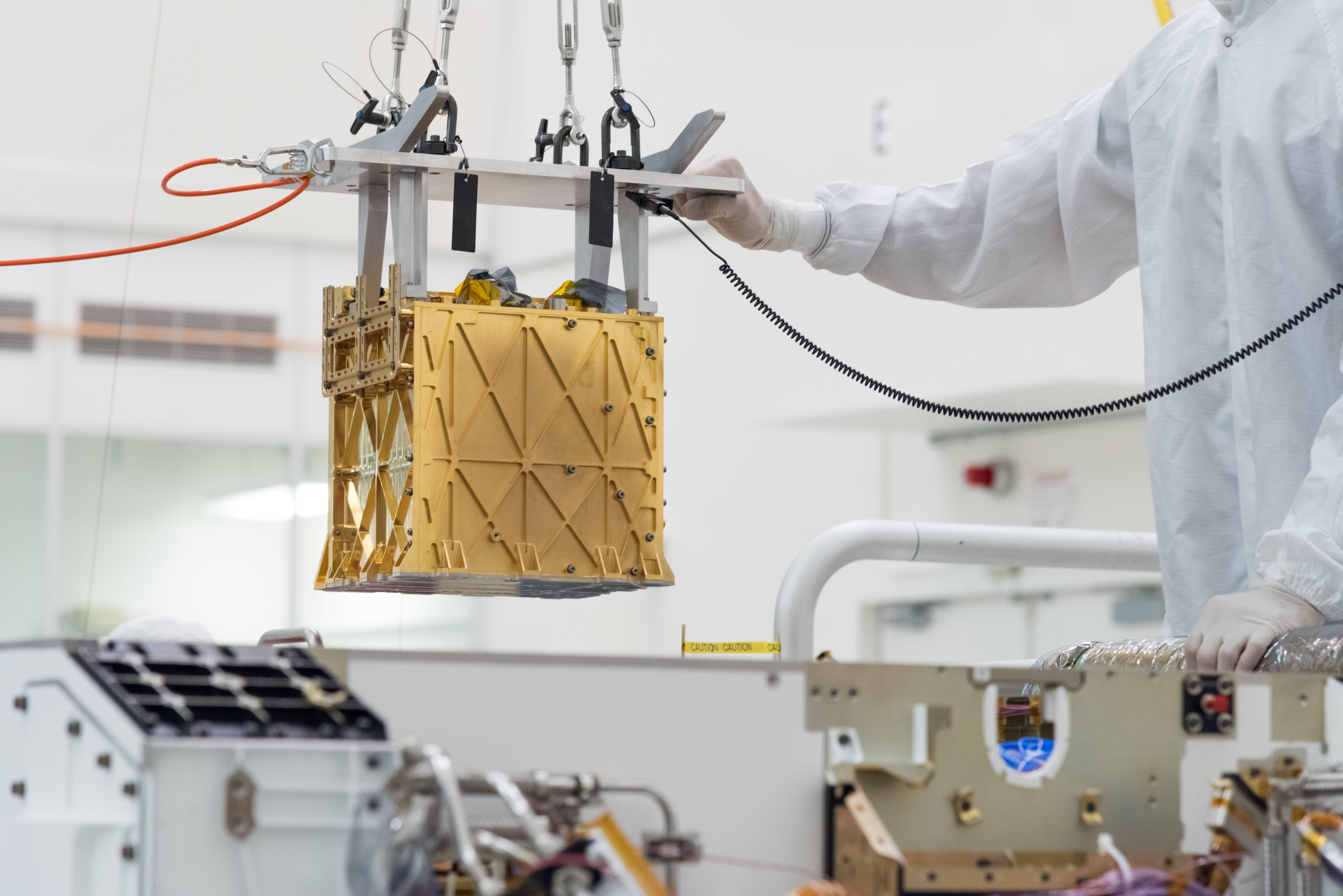 Technicians at NASA's Jet Propulsion Laboratory in La Cañada Flintridge, California, lower the Mars Oxygen In-Situ Res