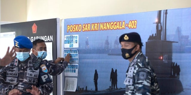 An Indonesian military official sets pictures of Indonesian Navy members on submarine KRI Nanggala that went missing while participating in a training exercise on Wednesday, at Ngurah Rai Airport, Bali, Indonesia, on Friday, April 23, 2021. (AP Photo/Firdia Lisnawati)