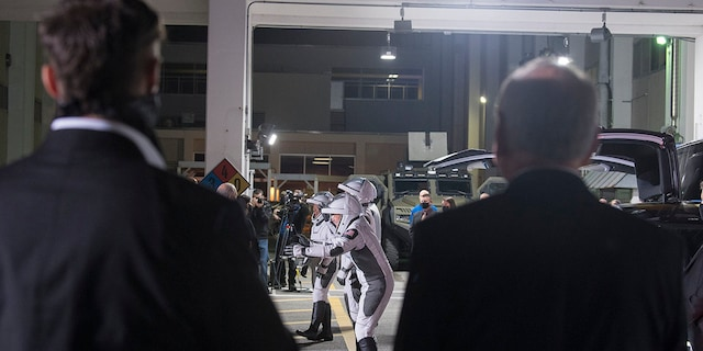 SpaceX Chief Engineer Elon Musk, left, and acting NASA Administrator Steve Jurczyk, right, watch as ESA (European Space Agency) astronaut Thomas Pesquet, Japan Aerospace Exploration Agency (JAXA) astronaut Akihiko Hoshide, and NASA astronauts Shane Kimbrough and Megan McArthur, prepare to depart the Neil A. Armstrong Operations and Checkout Building for Launch Complex 39A to board the SpaceX Crew Dragon spacecraft for the Crew-2 mission launch, Friday, April 23, 2021, at NASA's Kennedy Space Center in Florida. (Aubrey Gemignani/NASA via AP)