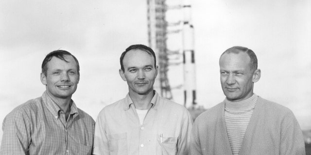 Apollo 11 astronauts Neil Armstrong, Michael Collins and Buzz Aldrin pose with their Saturn V in the background in this NASA handout photo dated May 20, 1969. REUTERS/NASA/Handout