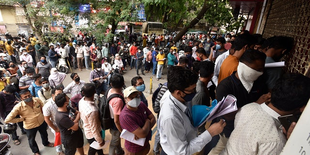 People wait in queues outside the office of the Chemists Association to demand the necessary supply of the anti-viral drug Remdesivir, in Pune, India. As India faces a devastating surge of new coronavirus infections overwhelming the health care system, people are turning to desperate measures to keep loved ones alive. (AP Photo, File)