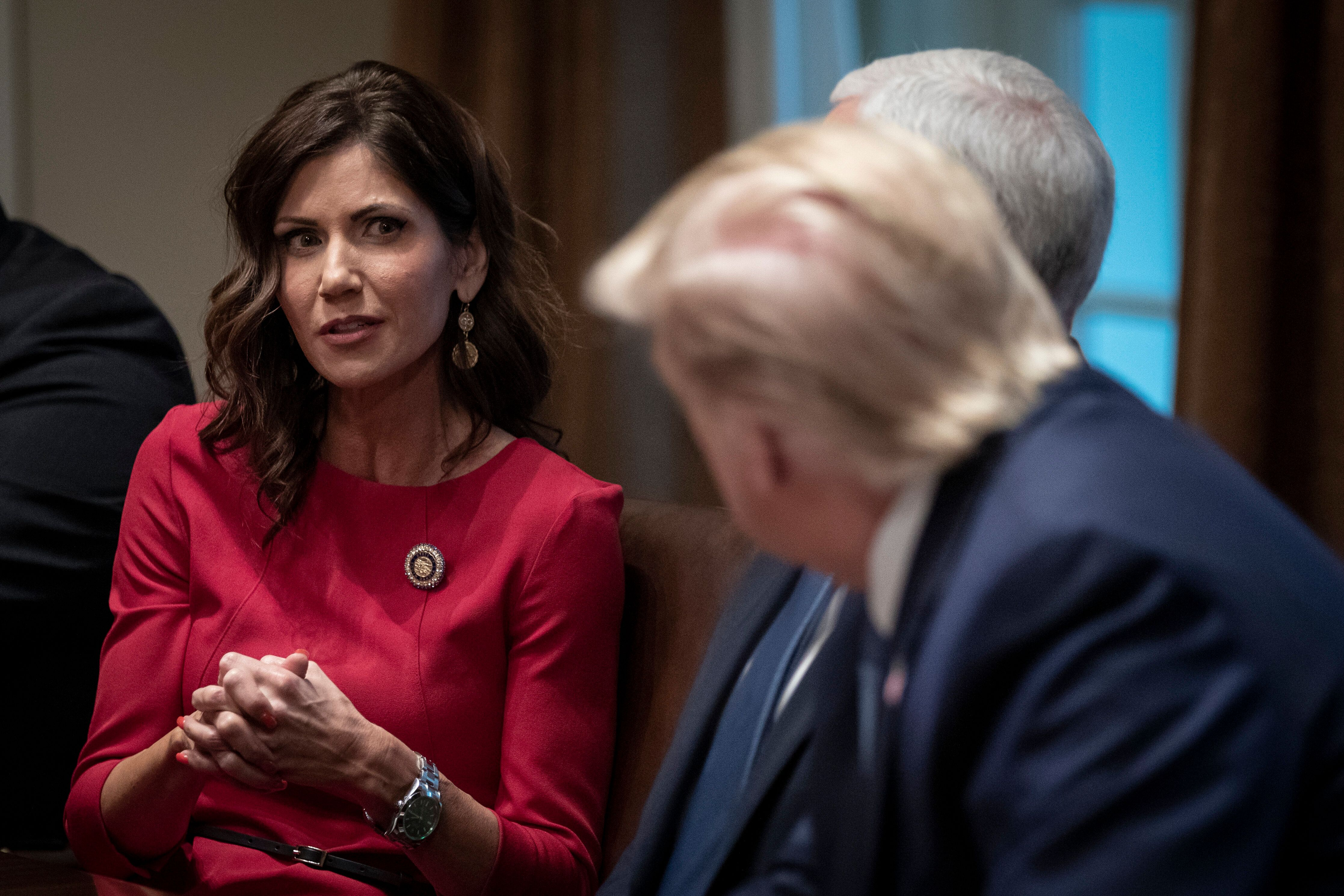 Kristi Noem, pictured talking to Donald Trump in 2019, believes the denial of the fireworks permit is politically motiv
