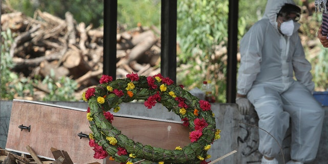 A wreath lies on the coffin of a COVID-19 victim before his cremation in Jammu, India, Friday, April 30, 2021. (Associated Press)