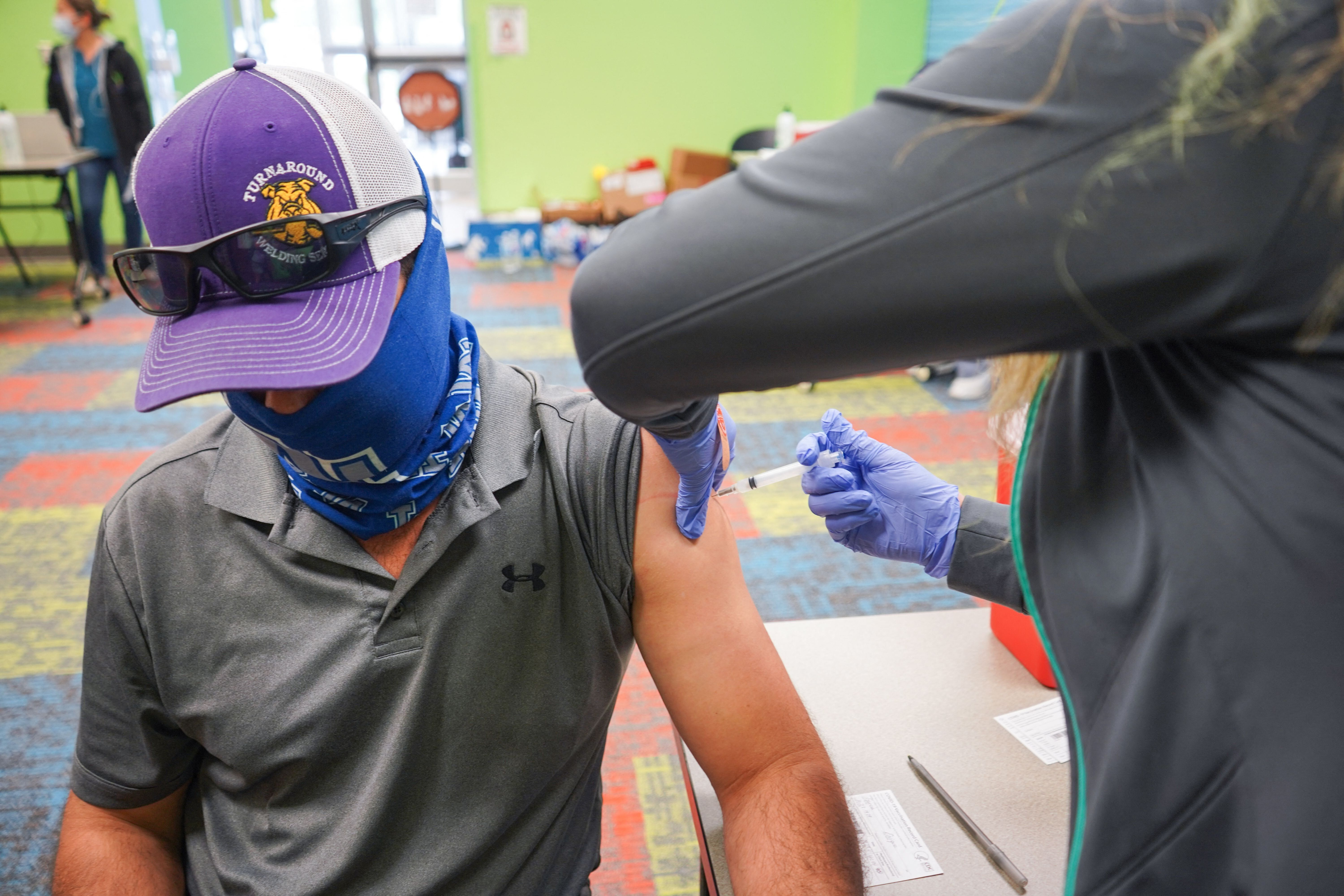 A health care worker vaccinates a man on April 30, 2021, at the Pasadena Public Library in Pasadena, Texas. (Photo by CECILE