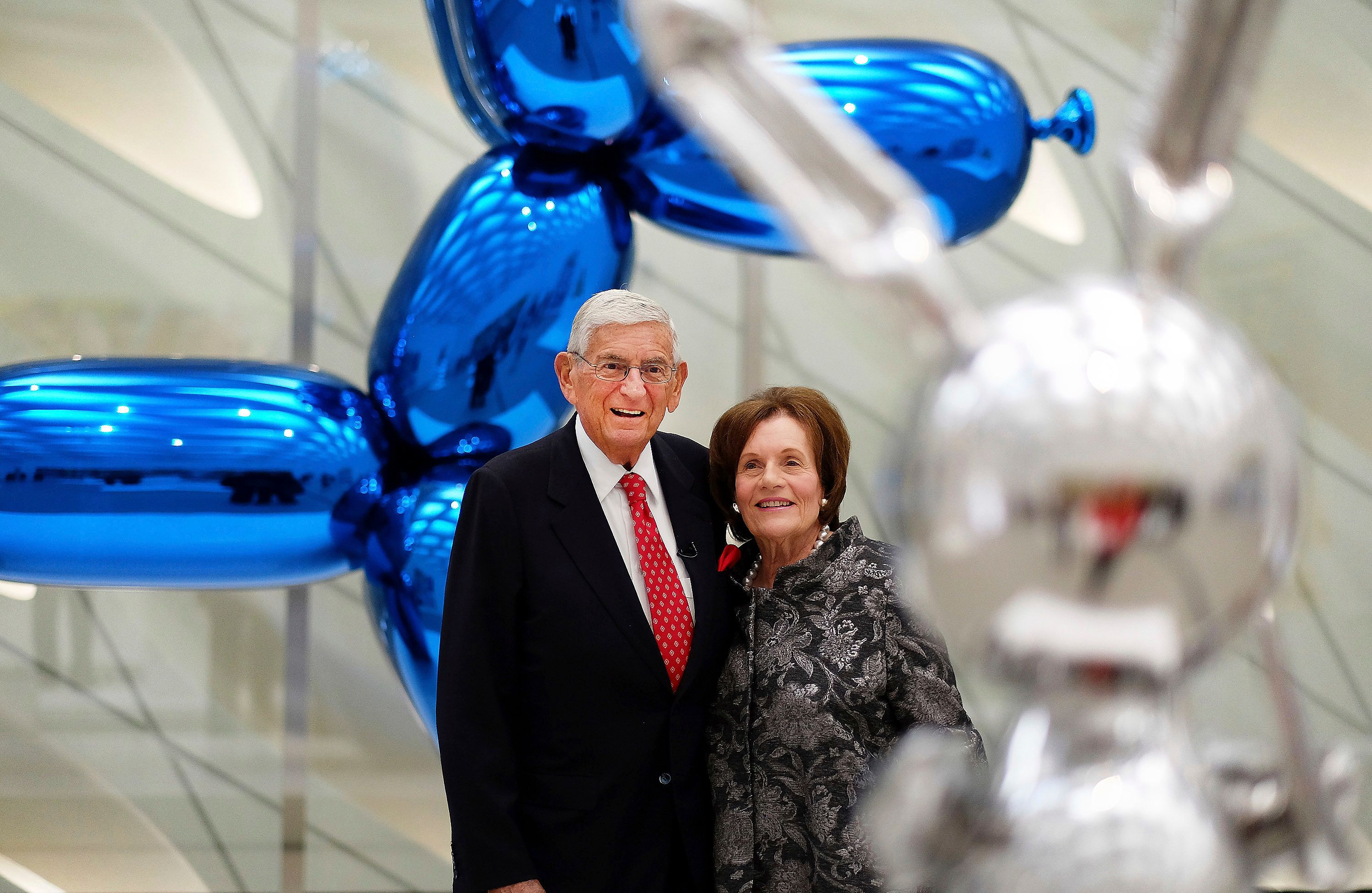 In this Sept. 16, 2015 file photo, Eli Broad and his wife, Edythe, stand for a photo amid Jeff Koons sculptures at his new mu