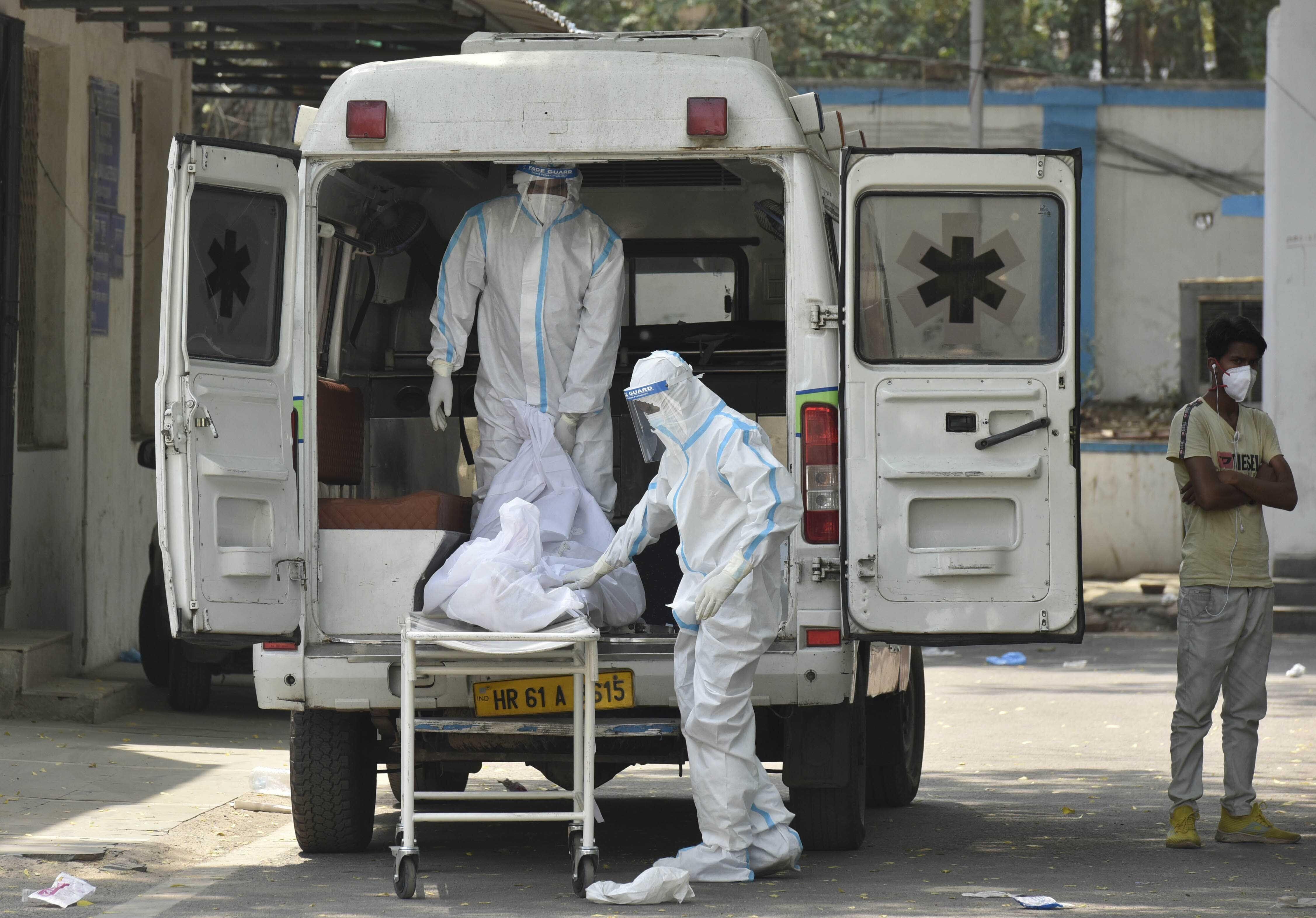 NEW DELHI, INDIA - APRIL 29: Hospital staff members shift dead body of a COVID-19 patient into an ambulance at Maulana Azad M