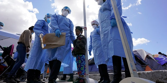 Baja California state health workers measure the height of a boy at a makeshift camp for migrants seeking asylum in the United States at the border crossing Friday, March 12, 2021, in Tijuana, Mexico. (AP Photo/Gregory Bull)